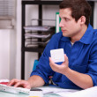 Stock Photo: Warehouse worker ordering new parts on Internet