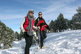 Couple walking in snowshoes — Stock Photo