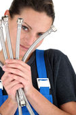 Female plumber with flexible hoses — Stock Photo