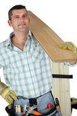 Handyman holding plank — Stock Photo