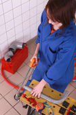 Female plumber sawing pipe — Stock Photo