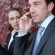 Businessman on a call whilst being watched by a colleague — Stock Photo