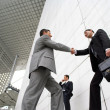 Businessmen shaking hands outside — Stock Photo