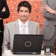 Musing laptop flanked by in suits — Stock Photo #8772058
