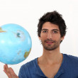 Man spinning a globe on his fingertips — Stock Photo #8772295