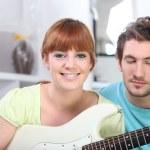 rödhåriga flicka spela gitarr i sovrum med pojkvän — Stockfoto