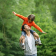 Little boy sat on father's shoulders — Stock Photo #8772564