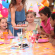Time to blow out the candles at a child&#039;s birthday party - Stock Photo