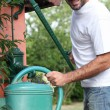 A mid aged man filling a watering can with a cast iron water pump — Stock Photo #8772929