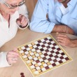 Royalty-Free Stock Photo: Senior woman playing checkers with a young man