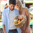 Couple with a basket at market — Stockfoto