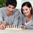 Attractive couple playing chess — Stock Photo #8775375