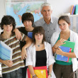 Teenagers standing with their teacher in a classroom — Stock Photo