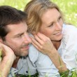 Stock Photo: Couple laying in field