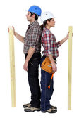 Male and female carpenters standing back to back — Stock Photo