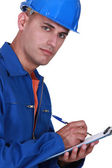 Inspector writing on clip-board — Stock Photo