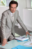 Man in a silver-grey suit purposefully standing by his desk — Stock Photo