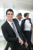 Smiling banker standing in a hall — Stock Photo