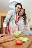 Couple making a salad in the kitchen — Stock Photo