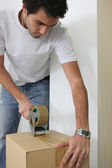 Young man wrapping cardboard — Stock Photo