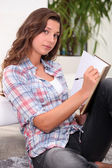 Woman writing in a book — Stock Photo