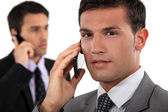 Businessmen talking on their mobile phones — Stock Photo