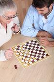 Senior woman playing checkers with a young man — Stok fotoğraf