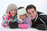 Young family lying in the snow — Stock Photo