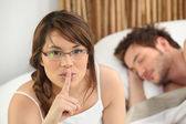 Woman telling you to be quiet while her lover sleeps — Stock Photo