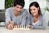 Attractive couple playing chess — Stock Photo