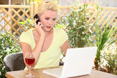Woman using her laptop outside a cafe — Stock Photo