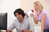 A man doing computer and a woman yelling on him with a megaphone — Foto de Stock
