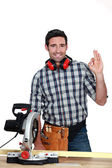 Man with circular saw making OK gesture — Stock Photo