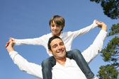 Little boy riding on his father's shoulders — Stock Photo