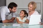 Parents and young daughter at laptop computer — Stock Photo