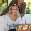 Woman painting as mother watches — Stock Photo #8780136