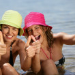 Two women at the beach giving the thumbs-up — Stock Photo
