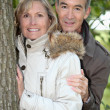 Mature couple out for an autumnal stroll in the woods — Stock Photo