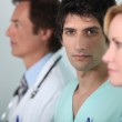 Young man in scrubs with other members of the medical staff — Stock Photo #8782015