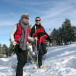 Stock Photo: Couple walking in snowshoes
