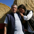 A farmer and his wife in front of bales of hay — Stock Photo