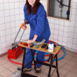Female plumber sawing pipe - Stockfoto