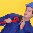 Tradesman's uniform stuck in the jaw of a pipe wrench — Stock Photo