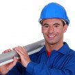 A construction worker carrying a long tube. — Stock Photo #8785524