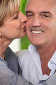 Mature woman kissing a smiling man on the cheek — Stock Photo