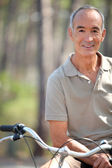 Middle-aged man riding bike — Stock Photo