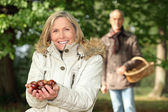 Mature woman in woods with husband showing chestnuts — Stock Photo
