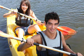 Couple paddling in a canoe — Stockfoto