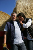 A farmer and his wife in front of bales of hay — Fotografia Stock