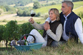 Man and woman tasting wine in a vineyard — Stock Photo